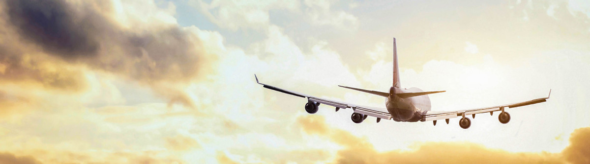 flying-airplane-in-the-sky-below-clouds-on-a-sunny-day-istock_000063753505_large-2-1200×335