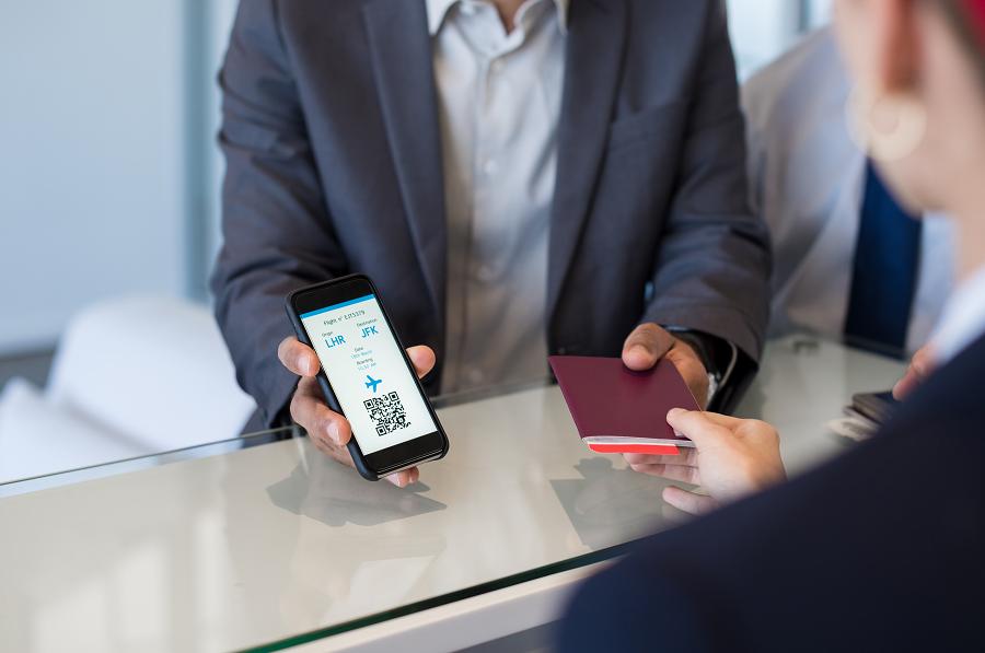 Person zeigt am Flughafen die Reiseunterlagen vor.