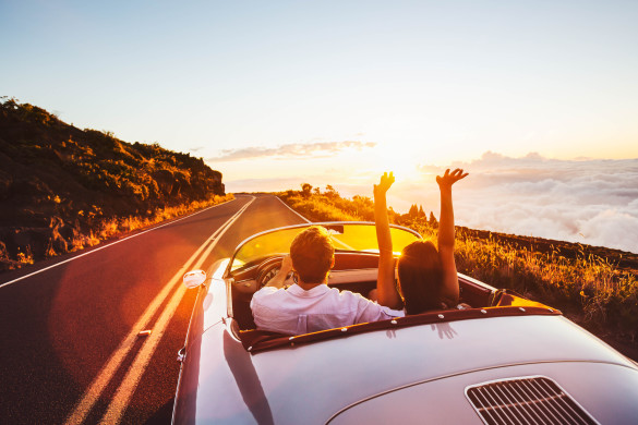 happy-couple-driving-on-country-road-into-the-sunset-in-classic-vintage-sports-car-shutterstock_305567459-2-585x390