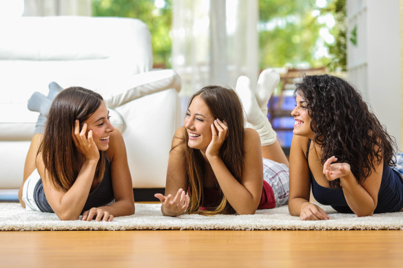 group-of-happy-teen-friends-talking-lying-on-the-floor-at-home-shutterstock_323664887-2-585x390