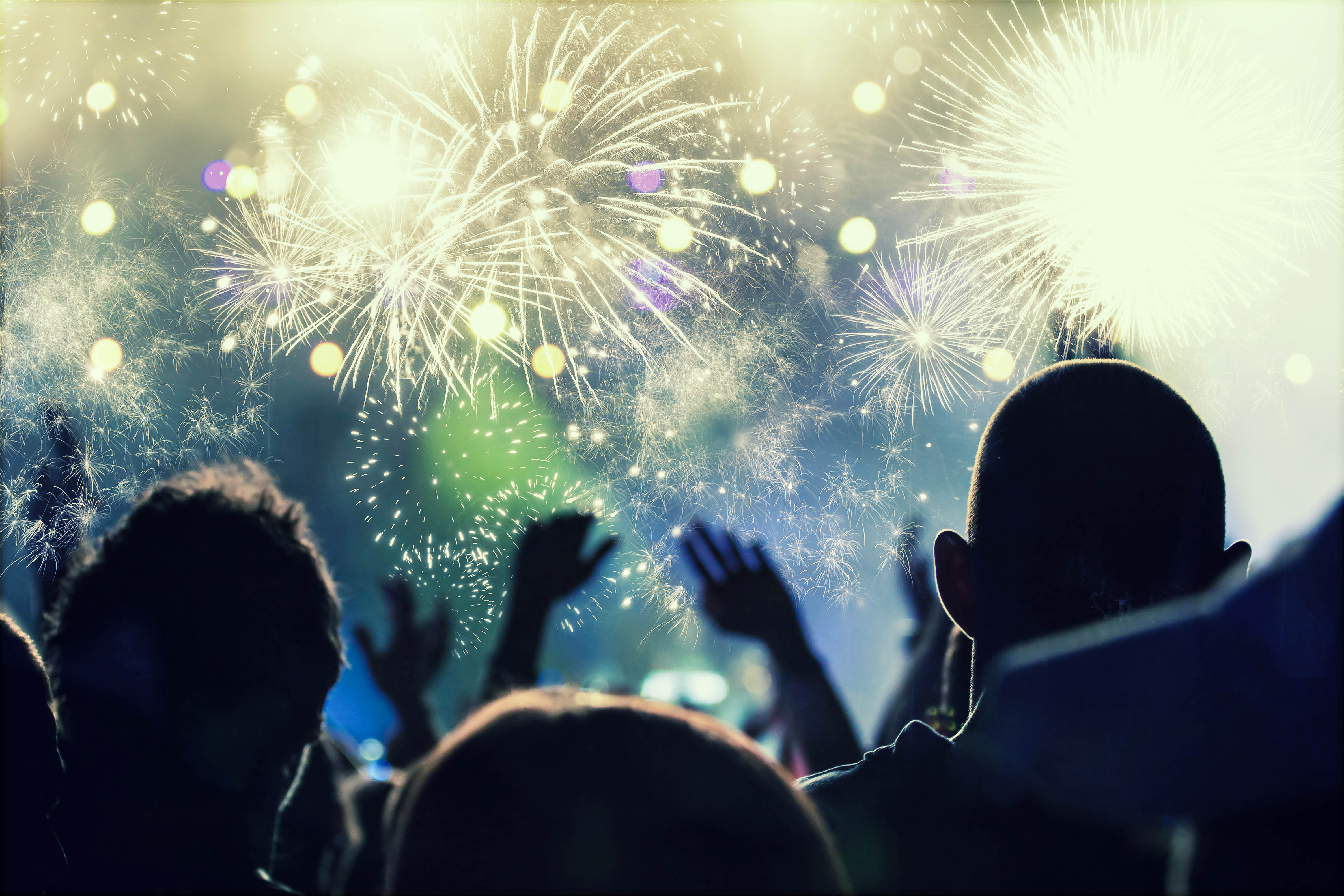 Cheering crowd and fireworks at New Year's Eve - people celbrating on open air