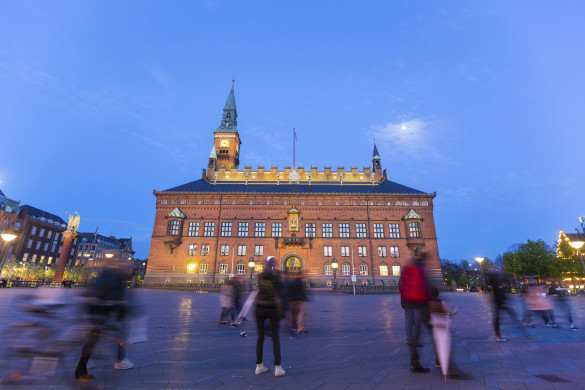 CIty hall in copenhagen, capital city of Denmark. Photo taken after sunset, during the blue hour. There are some blurred persons walking on the square. Travel and architecture themes.