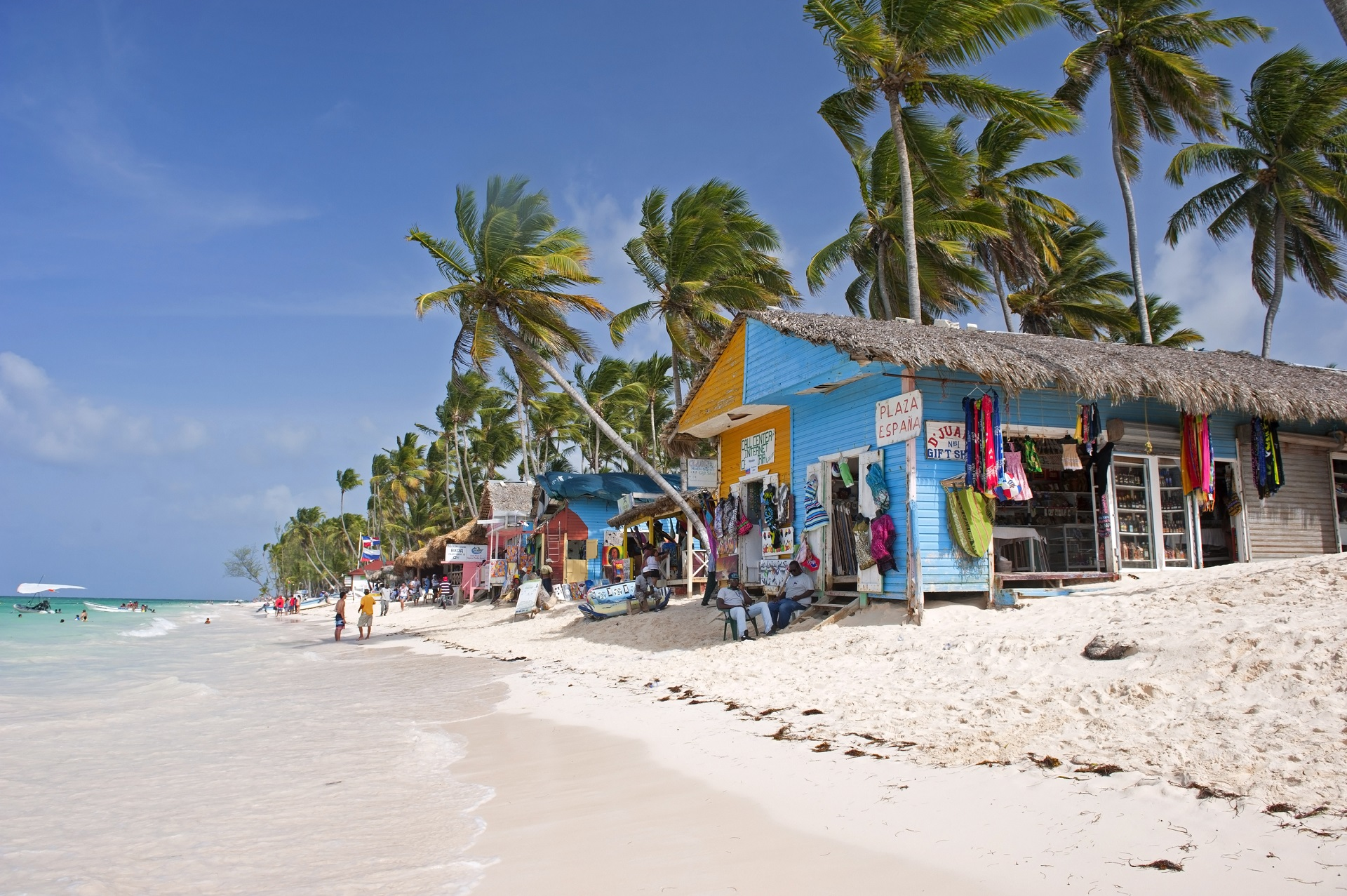 Punta Cana, Dominican Republic- July 20, 2013: Tourist walking on the beach and take a tour of the bungalows-stalls with souvenirs. Locals sitting in front of stalls