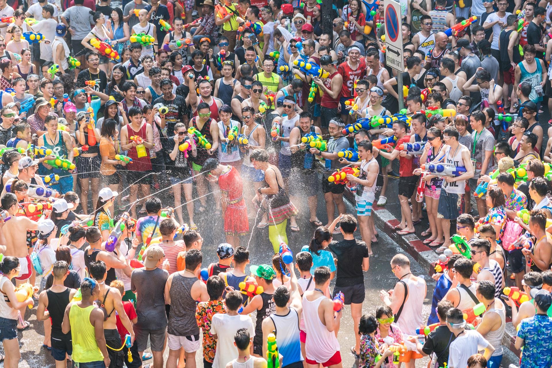 Thais bespritzen Touristen auf der Straße beim Songkran Festival.