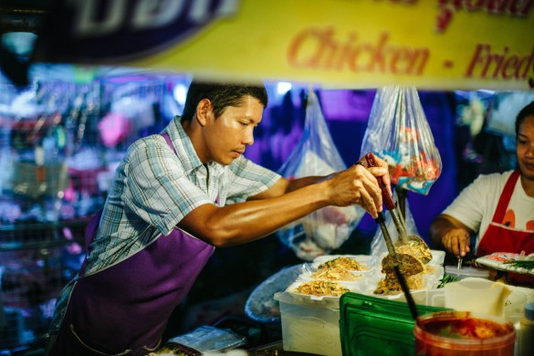 Patong, Thailand - February 15, 2013: Night food market in Thailand. Image was taken in Phuket, near the Banzaan market. Thai food vendor selling barbecue chicken. The area is popular with toursits and lively in the evenings especially with many street food vendors.