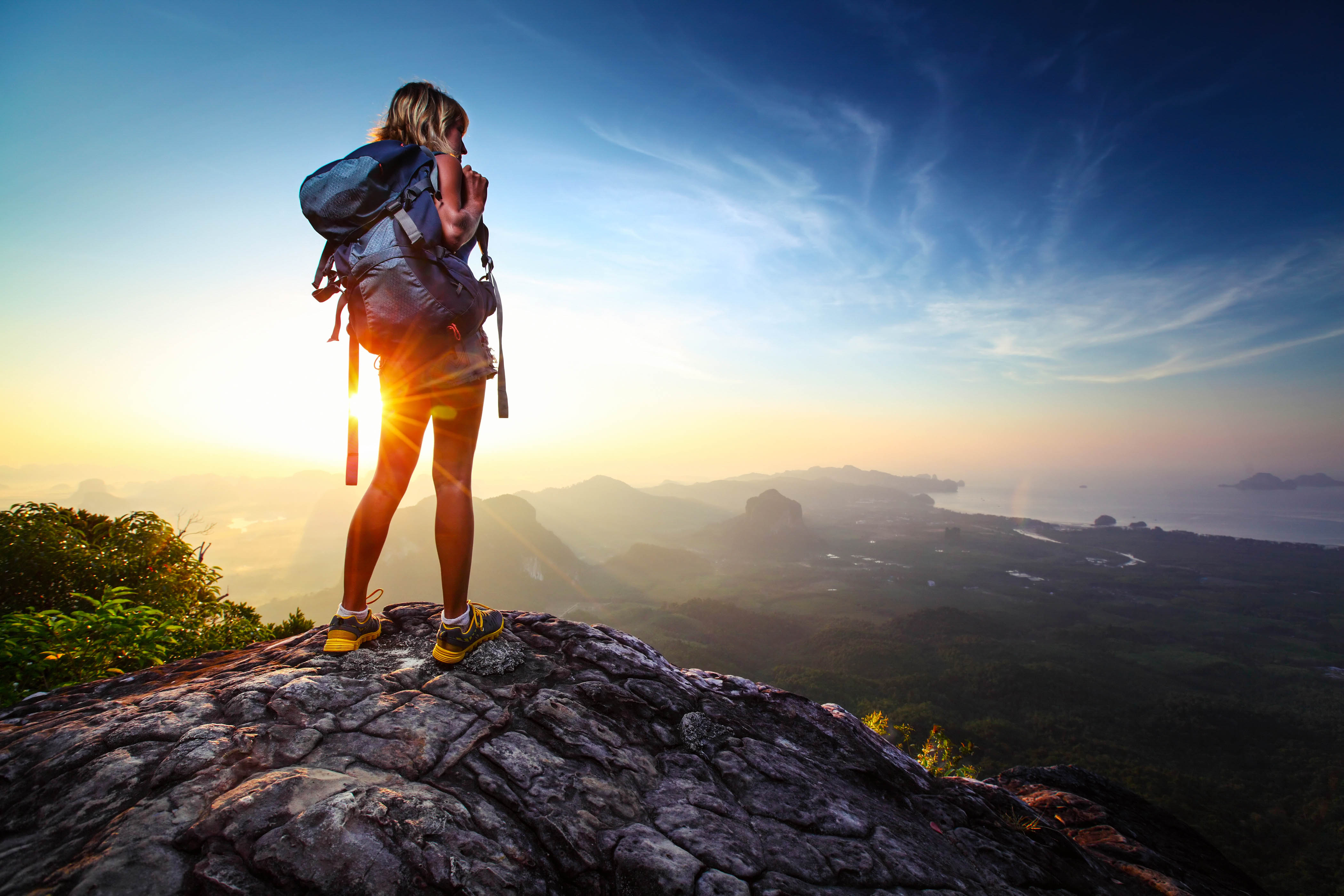 Young lady hiker standing with backpack on top of a mountain and enjoying sunrise