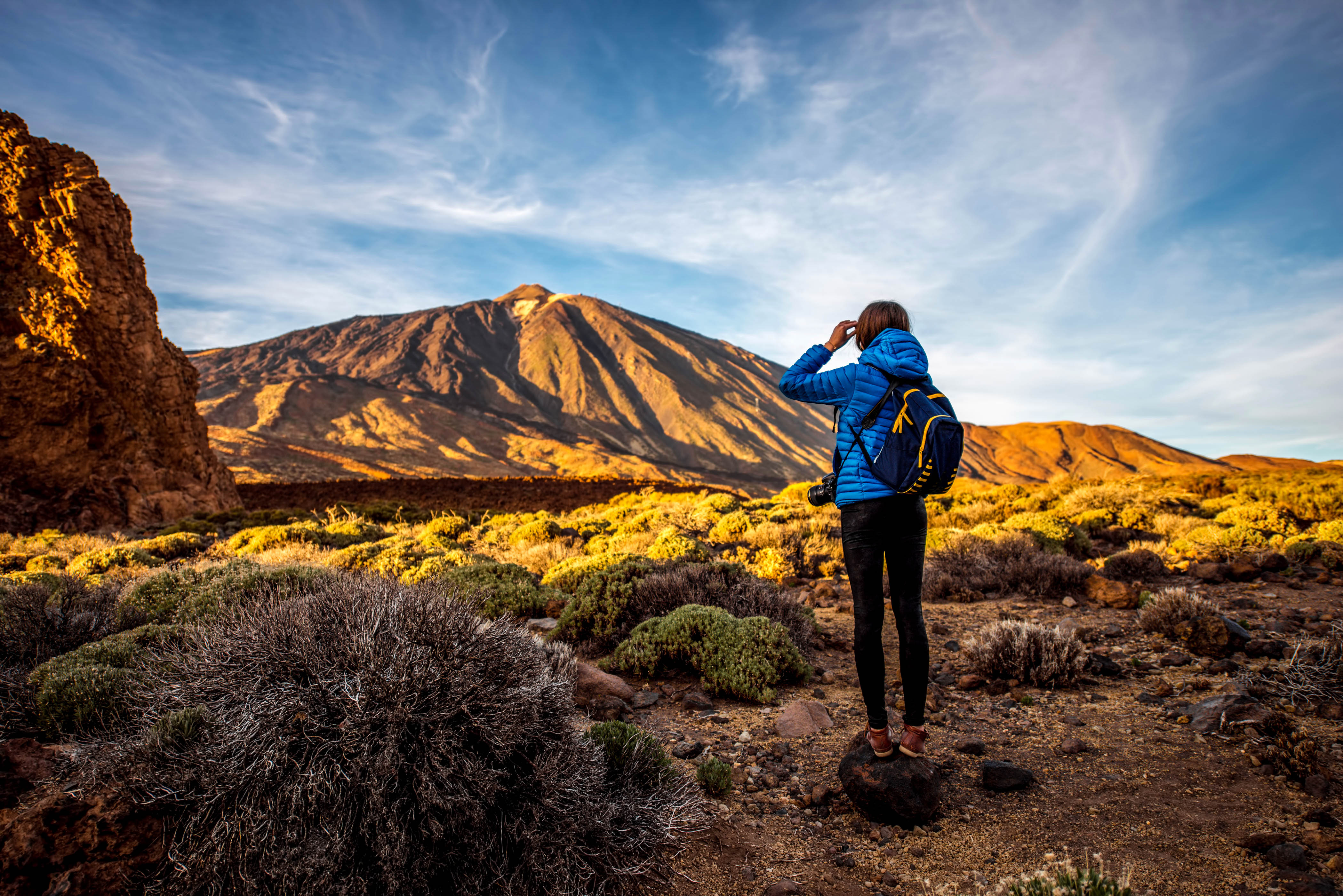 Young female traveler with bacpack standing on the stone and looking forward in Teide park on Tenerife island