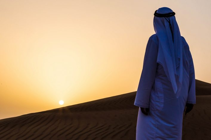 An Arab admiring the sunrise in desert, Dubai
