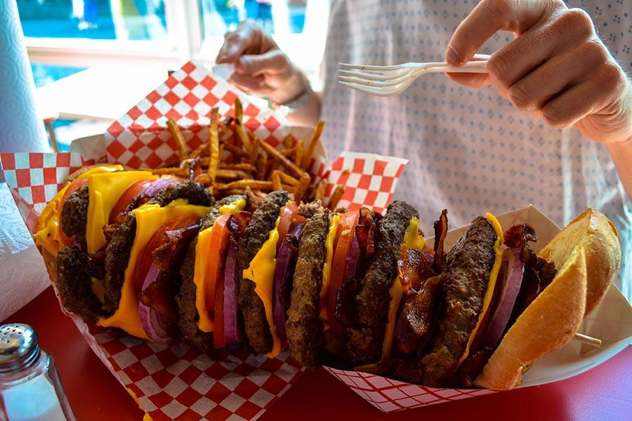 Einen-riesigen-gestapelten-Burger-und-Pommes-frites-iStock-832279284-1