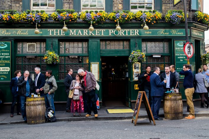 London, UK  – April 08, 2015: People traditionally drink beer near the pub after a working day
