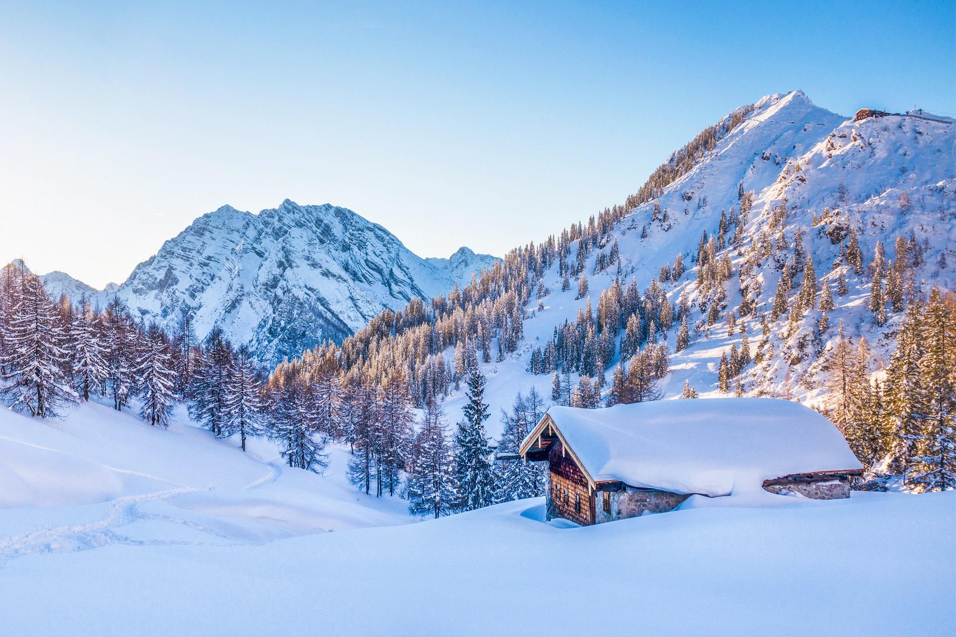Eine schöne Berghütten im verschneiten Bayern bei Sonnenuntergang.