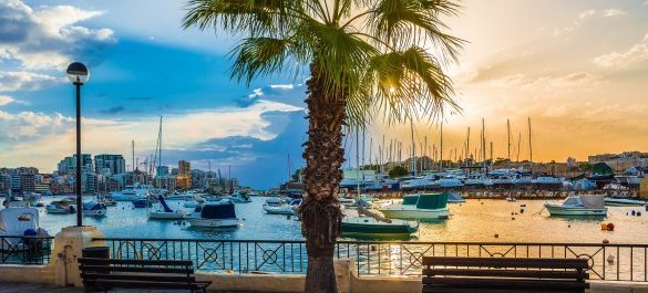 beautiful-sunrise-with-benches-palm-tree-and-sailboats-at-sliema-bay-malta-shutterstock_357393446-2