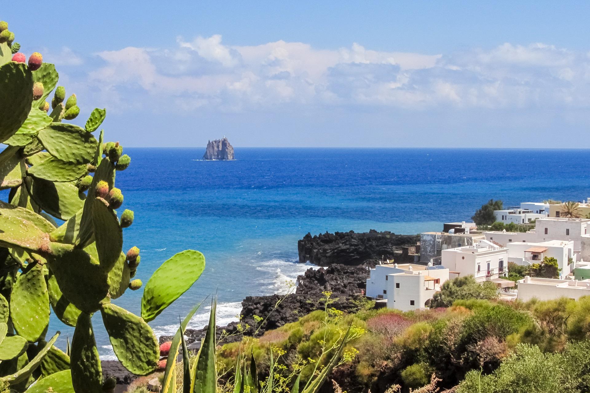 Die Küste der Insel Stromboli ist geprägt vom Kontrast zwischen schwarzem Vulkangestein, weißen Häusern und dem türkisen Meer.