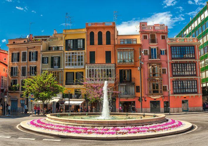 Bunte Häuser und ein Brunnen im Herzen von Palma de Mallorca.
