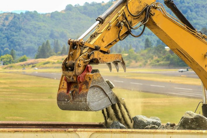 a-large-tracked-hoe-or-excavator-working-at-a-construction-site-to-extend-an-airport-runway-shutterstock_108570776-2