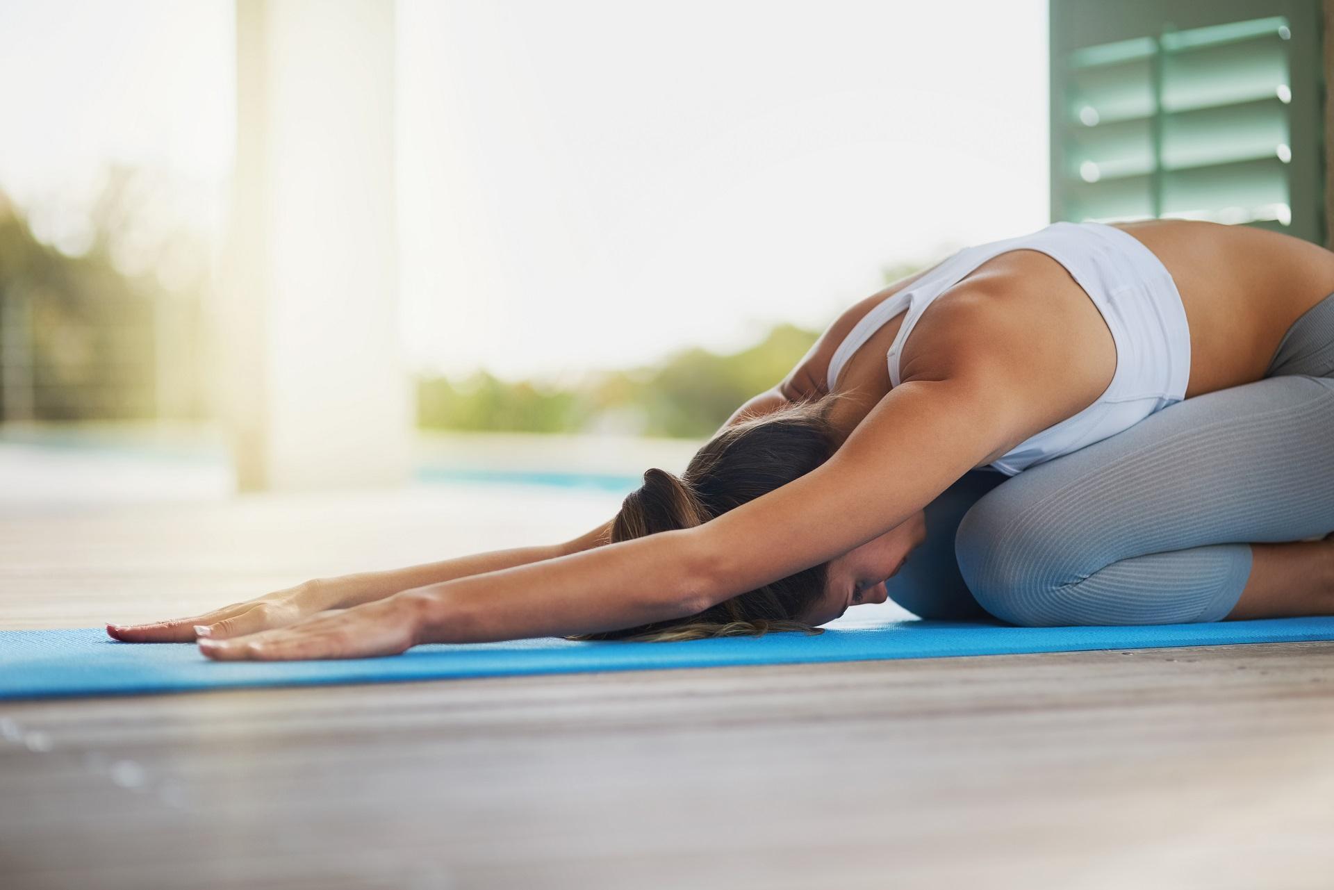 Frau macht Yoga am Flughafen.