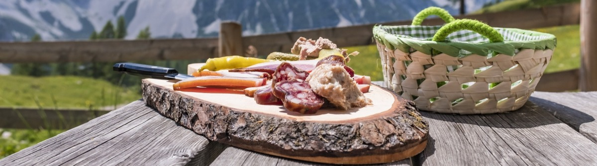 Brettljause-on-wooden-table-on-Klagenfurter-Huette-with-view-to-mountain-Weinasch-in-Karawanks-shutterstock_668489185-1