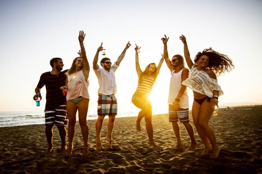 Junge Menschen tanzen am Strand in Griechenland