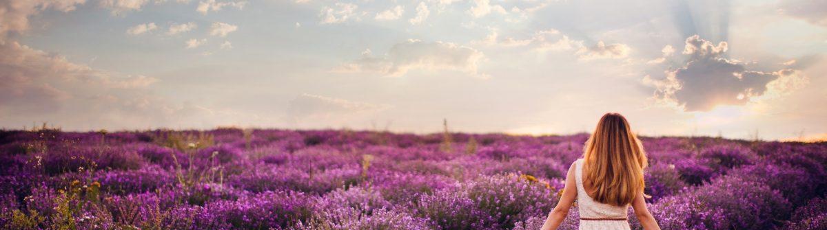 Eine Frau läuft durch ein Lavendelfeld in der Provence