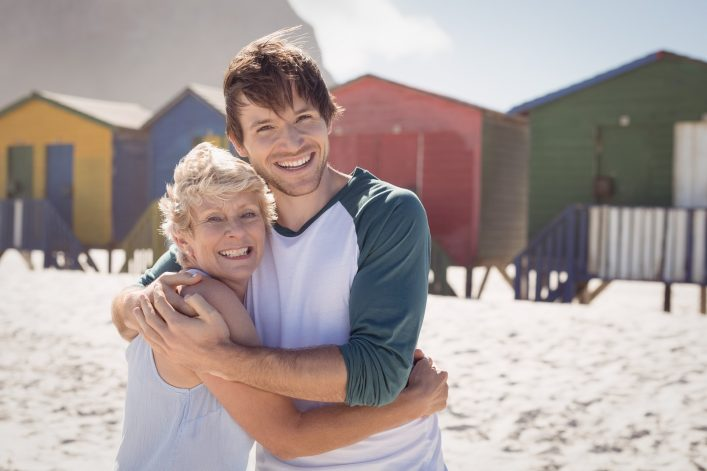Portrait of happy mother embracing her son at beach