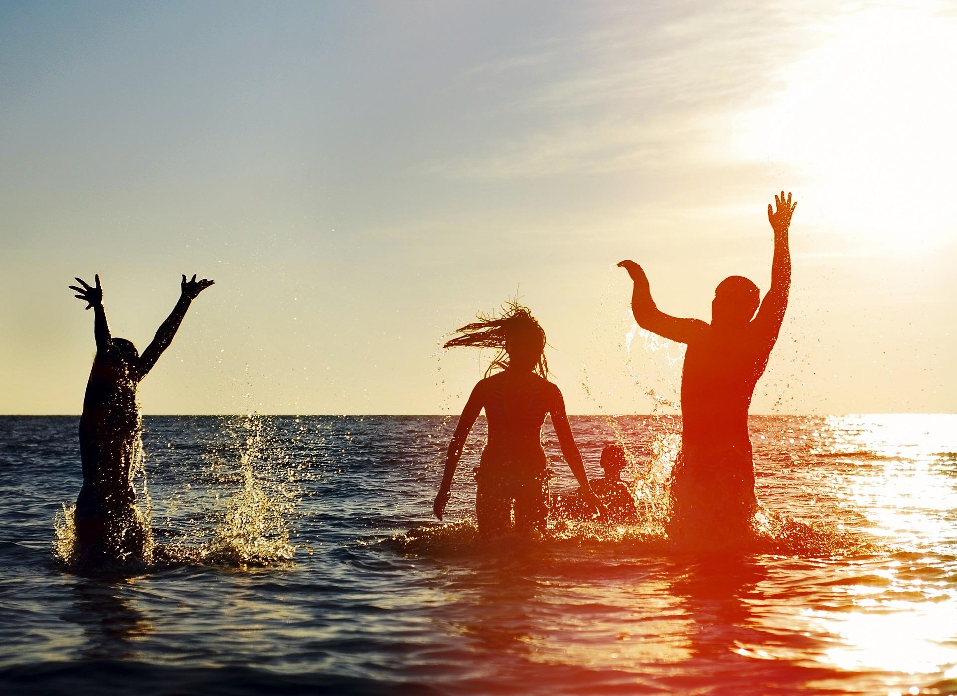 Vier Menschen springen freudig ins Meer