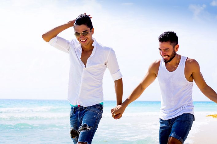 Zwei Männer laufen händchenhaltend den Strand entlang