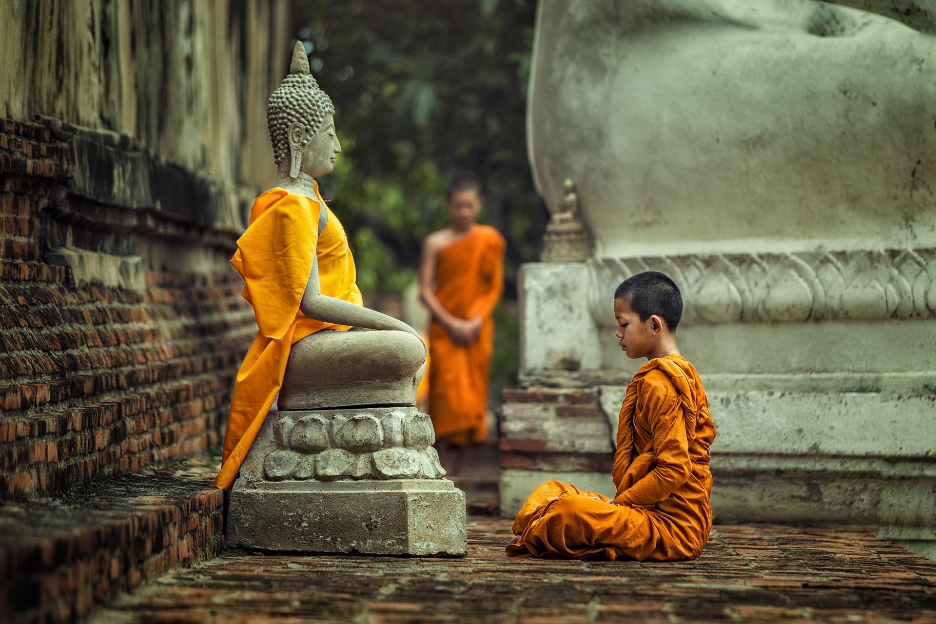 Ein junger Mönch vor einer Buddhastatue in Kambodscha