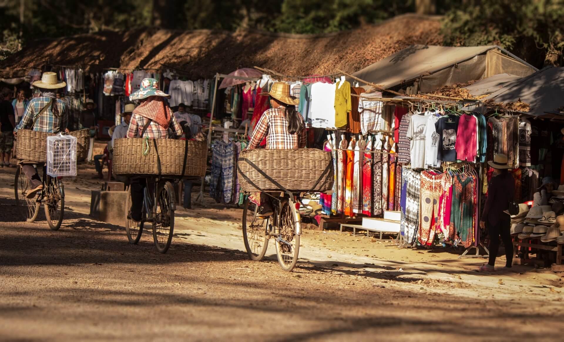 Frauen transportieren ihre Waren auf Fahrrädern in Kambodscha