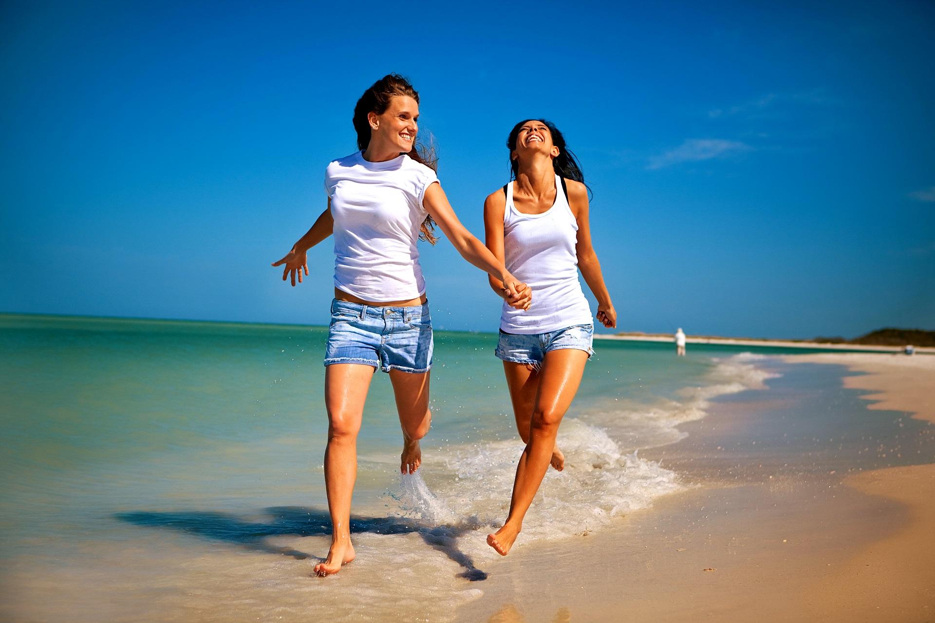 Zwei Frauen laufen Hand in Hand den Strand entlang