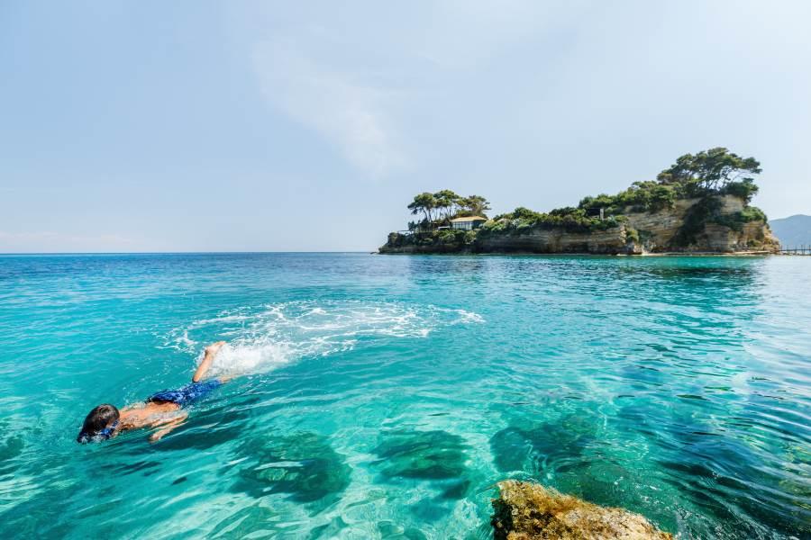 Junge schnorchelt im türkisen Wasser bei Zakynthos