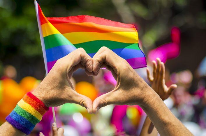 Zwei Hände bilden ein Herz vor einer Regenbogen Fahne