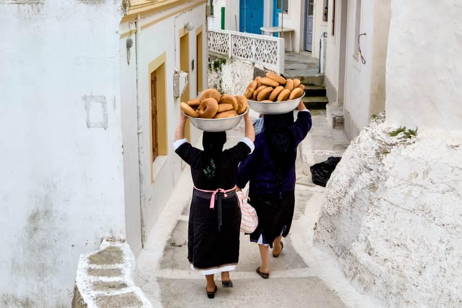 Traditionell gekleidete Griechinnen, die Brot für das Osterfest backen