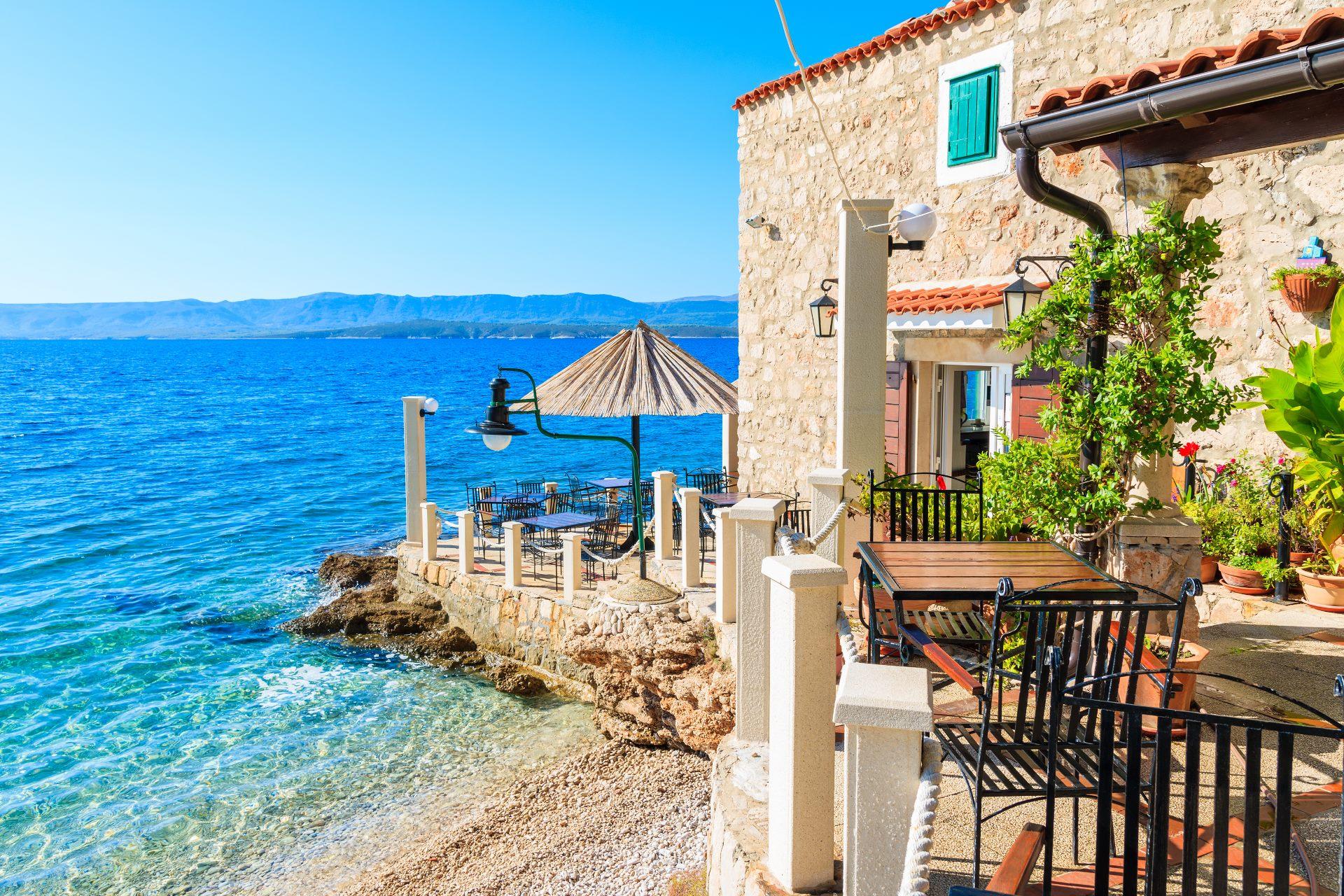 Terrasse mit Stühlen am Meer auf der Insel Brac in Kroatien