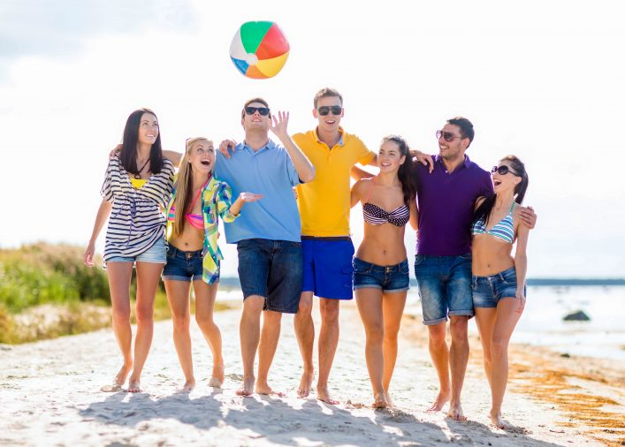 Bei gutem Wetter läuft eine Gruppe junger Leute über den Strand.