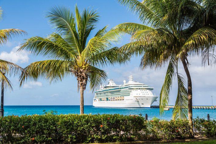 Ein Kreuzfahrtschiff liegt in einem kleinen Hafen in der Karibik vor Anker