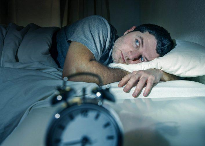 Ein Mann liegt im Bett und kann nicht schlafen.