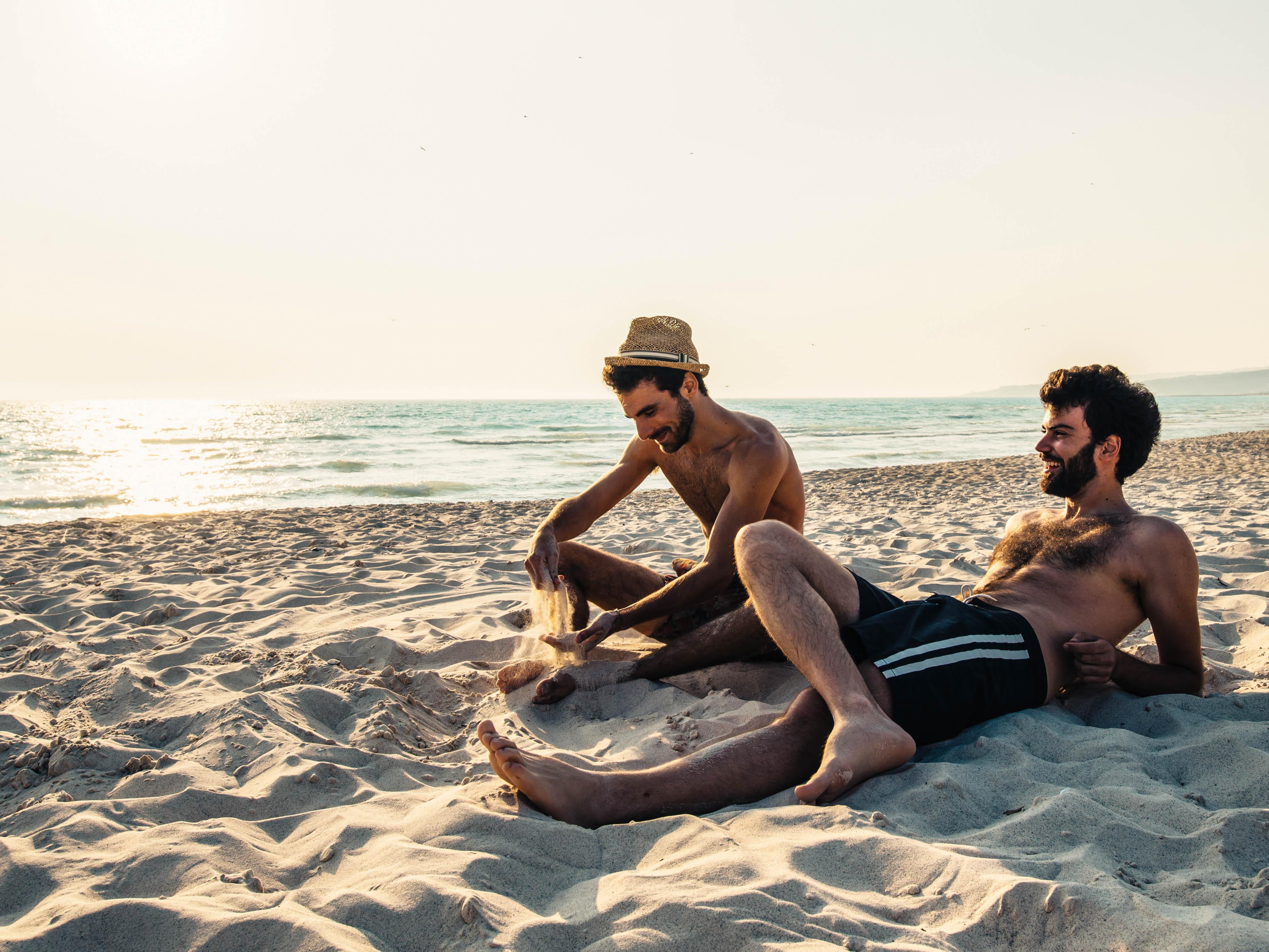 Zwei Männer liegen im Sand und lachen