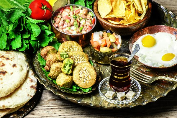 Arabisches Frühstück in Ägypten mit Chai, Ful aus Saubohnen, Spiegeleiern, Fladenbrot und Gemüse