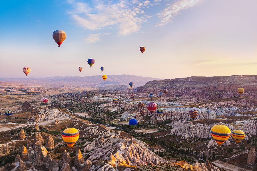 Heißluftballone fliegen über die Landschaft in Kappadokien