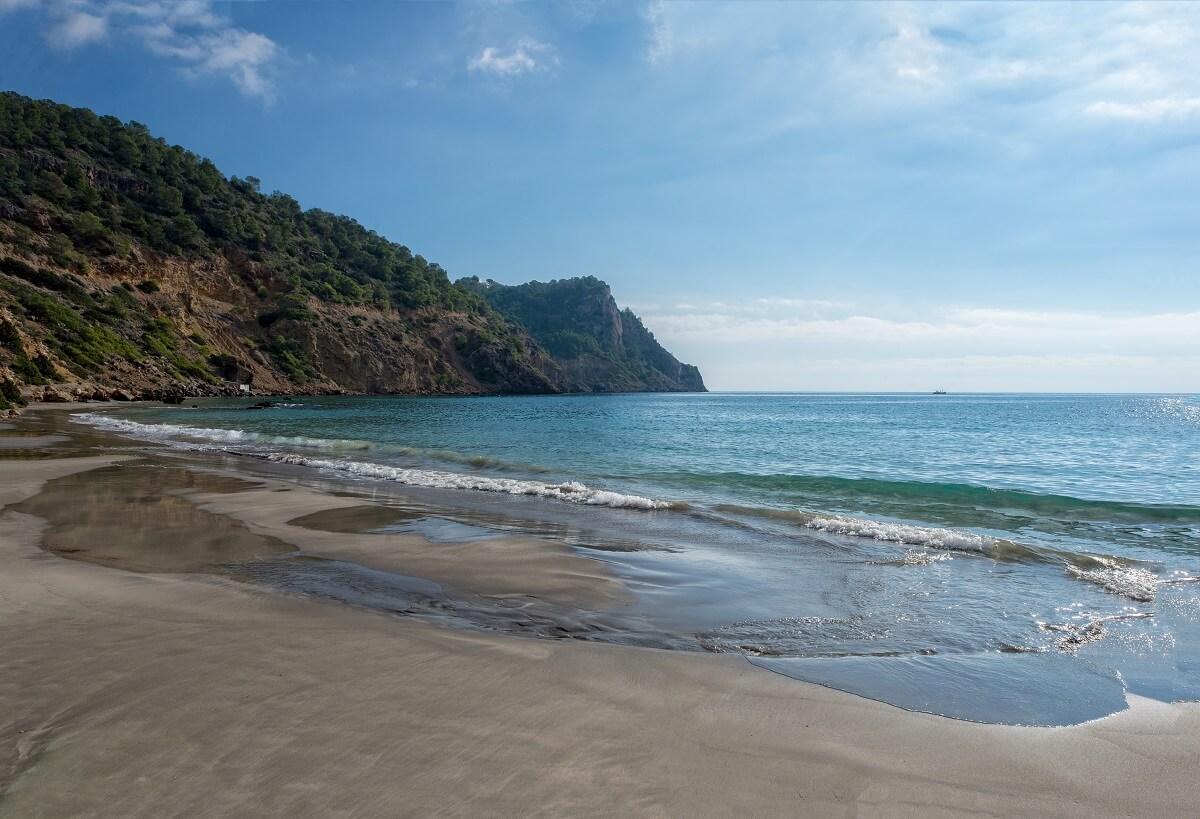Der Strand Cala Boix auf Ibiza in Spanien besticht mit seinem dunklen Sand