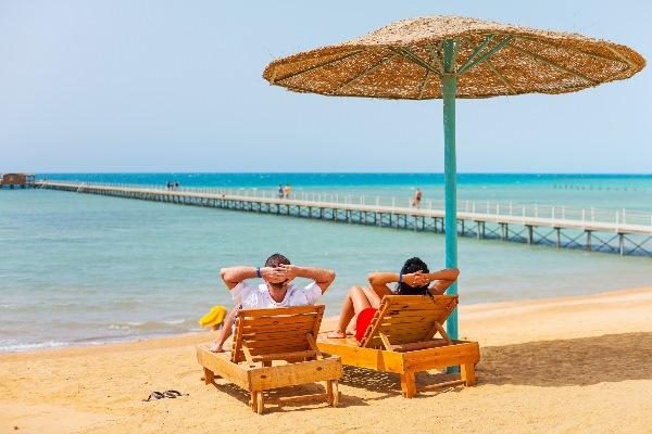 Ein Pärchen sitzt auf zwei Liegen unter einem Schirm am Strand von Hurghada in Ägypten und blickt aufs Rote Meer