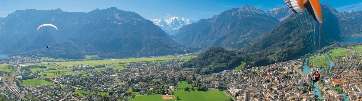 Interlaken: Paraglider im Flug ueber Interlaken
