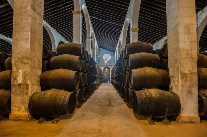 Sherry barrels line a walkway in a bodega in Jerez, Spain