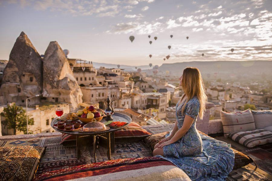 Frau sitzt auf dem Boden und betrachtet Heißluftballons