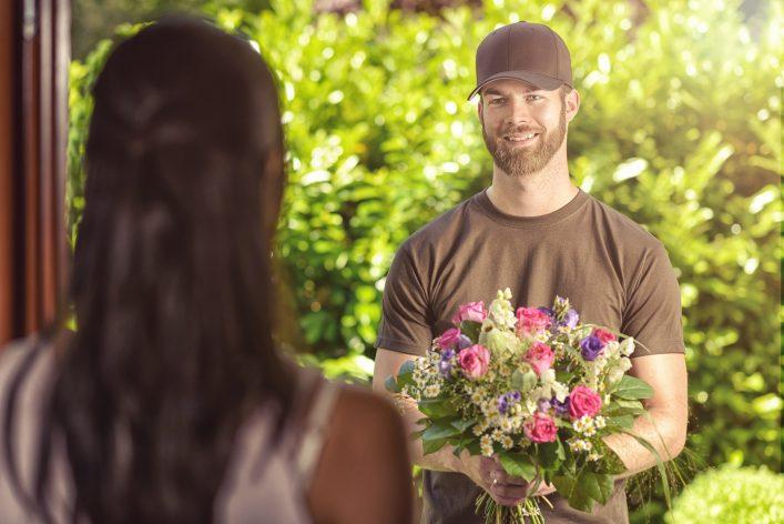 Blumenlieferant_übergibt_Frau_Blumen_shutterstock_292093511