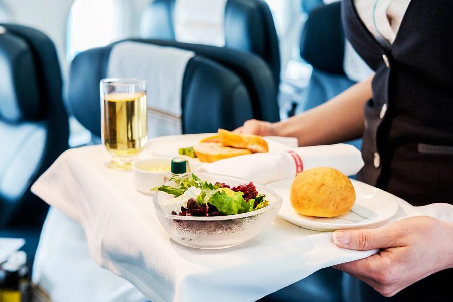 Ein Flugbegleiter serviert einem Gast an Bord eines Flugzeuges seine Mahlzeit