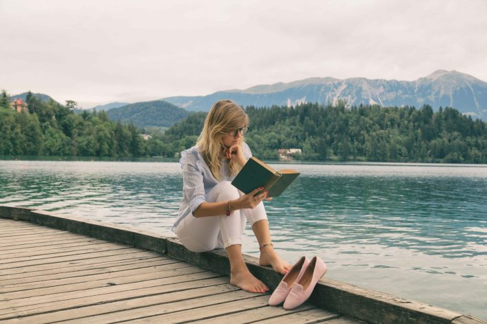 Pretty-woman-enjoying-on-the-lake-and-reading-a-book._shutterstock_692857189-e1534850085858