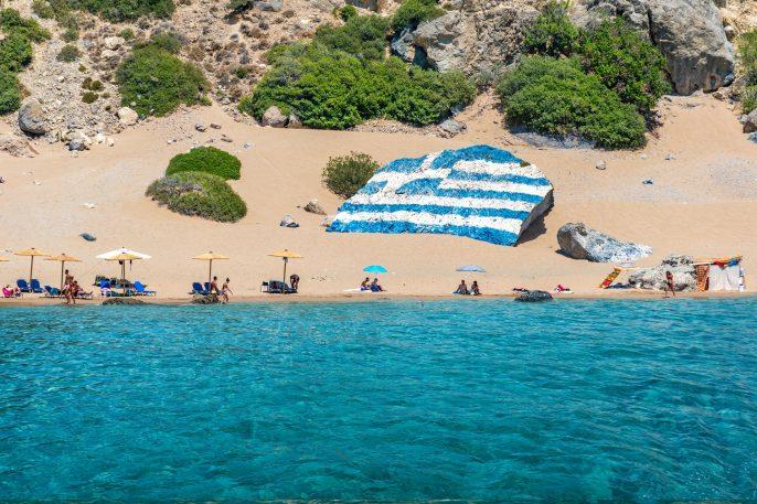 Griechische Flagge am Strand Tsambika auf Rhodos, Griechenland shutterstock_782944207