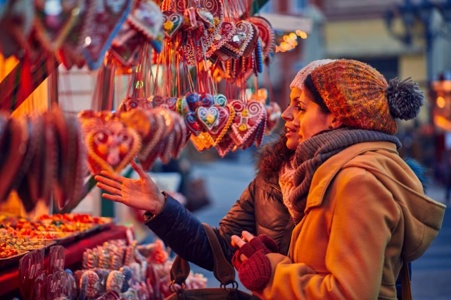 Freundinnen an einem Stand auf dem Weihnachtsmarkt