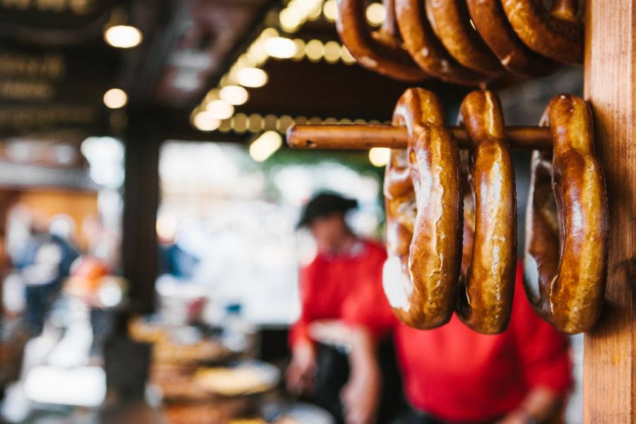 shutterstock_771306997_Traditional-pretzels-called-Brezel-hang-on-the-stand-against-the-background-of-a-blurred-street-market-and-people-on-holiday_900x600